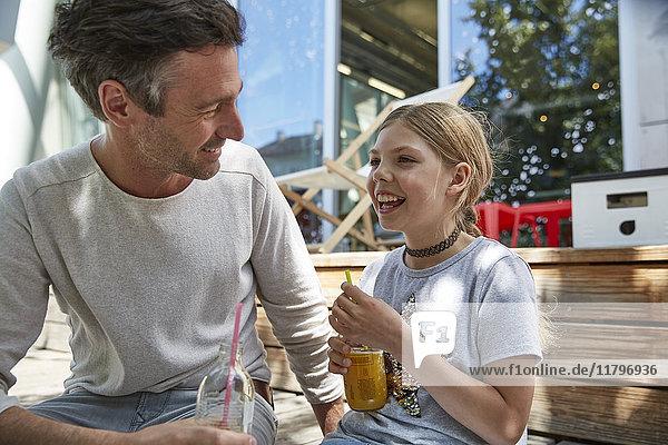 Glücklicher Vater und Tochter mit Getränken in einem Outdoor-Café