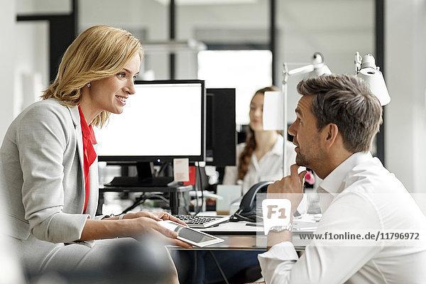 Geschäftsfrau und Geschäftsmann diskutieren am Schreibtisch im Büro