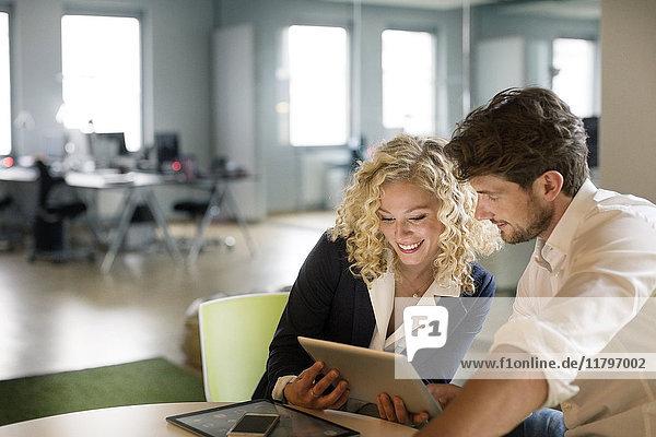 Geschäftsmann und Frau besprechen Projekt im Büro  mit digitalem Tablett