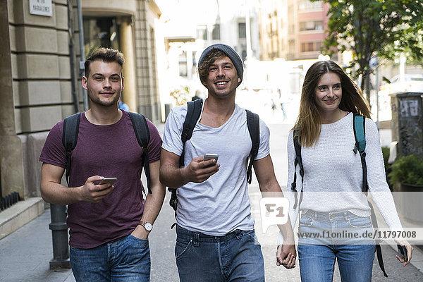 Freunde mit Handys  die in der Stadt spazieren gehen.