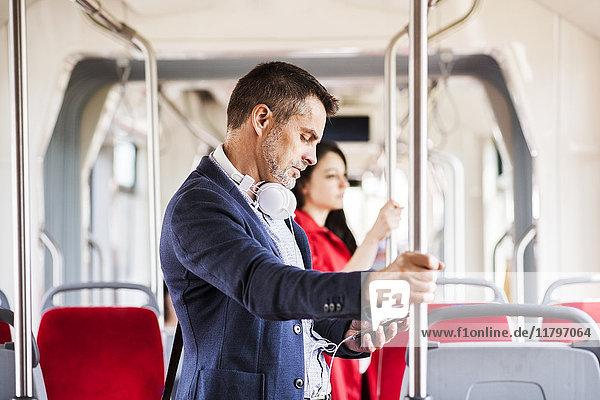 Geschäftsmann mit Smartphone und Kopfhörer auf Busfahrt