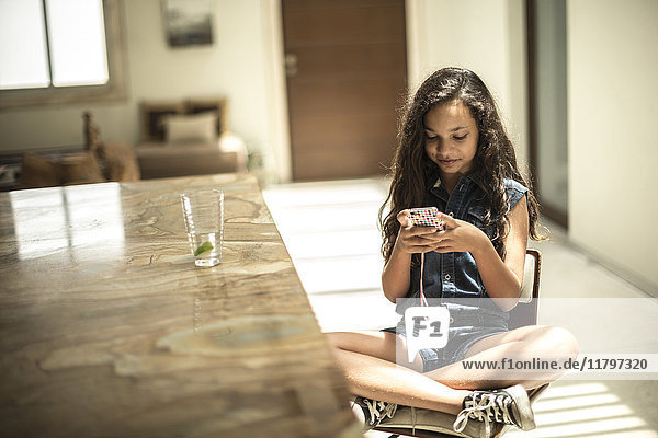 A girl sitting looking at a mobile phone screen.