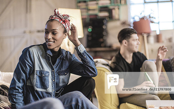 Young woman wearing headscarf and young man holding beer bottle sitting indoors on a sofa  smiling.