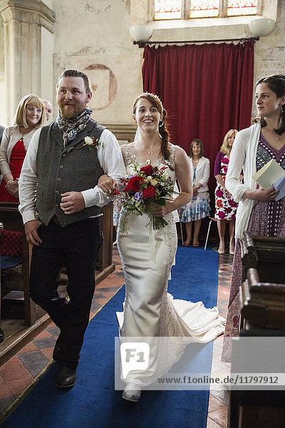 Lächelndes Brautpaar beim Gang über die Insel in einer Kirche.