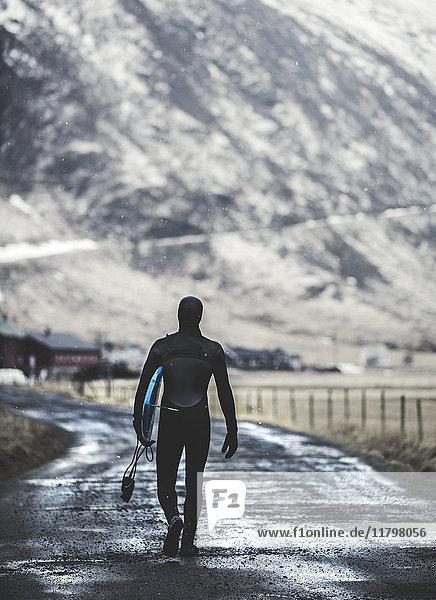 Rückansicht eines Surfers  der in einem Neoprenanzug und mit einem Surfbrett auf einer Straße geht.
