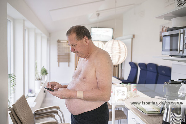 Shirtless man texting on cell phone