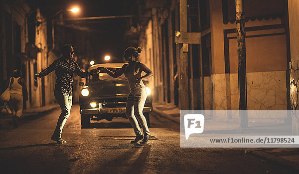 A man and a woman dancing together in front of a classic 1950s car in a street at night.