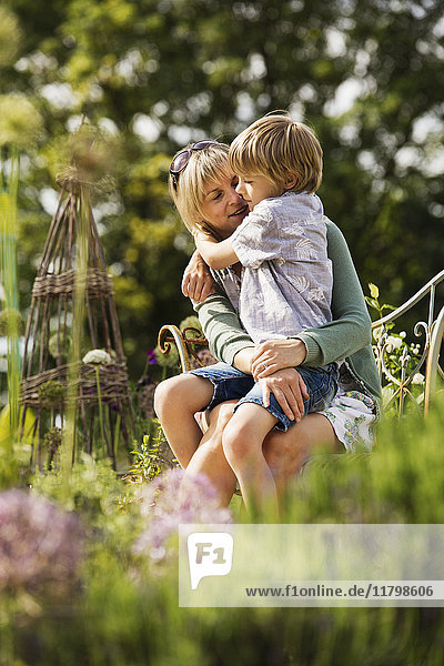 Frau sitzt in einem Garten mit einem Jungen auf dem Schoß und umarmt sich.