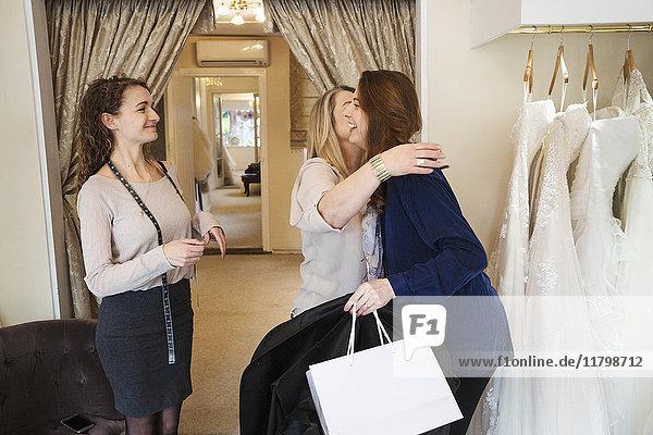 Drei Frauen in einem Brautkleidergeschäft  eine umarmt und begrüßt einen Kunden. Eine Brautkleider-Boutique.