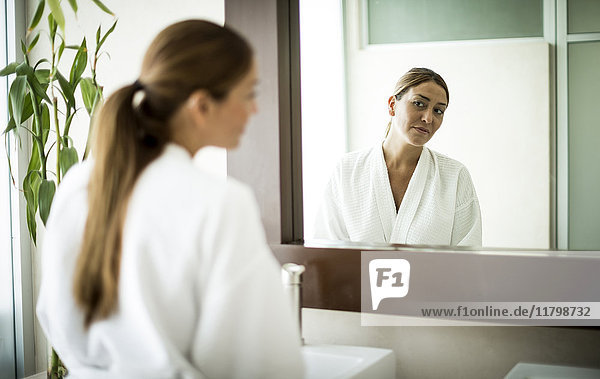 A woman standing in front of a bathroom mirror and looking at her reflection.