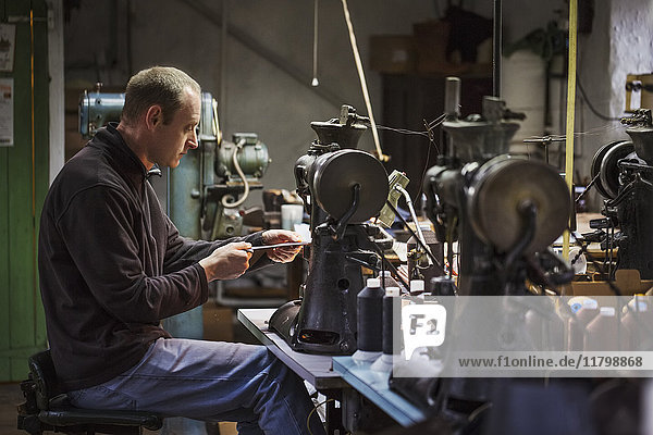 Man sitting at a sewing machine in a shoemaker's workshop.
