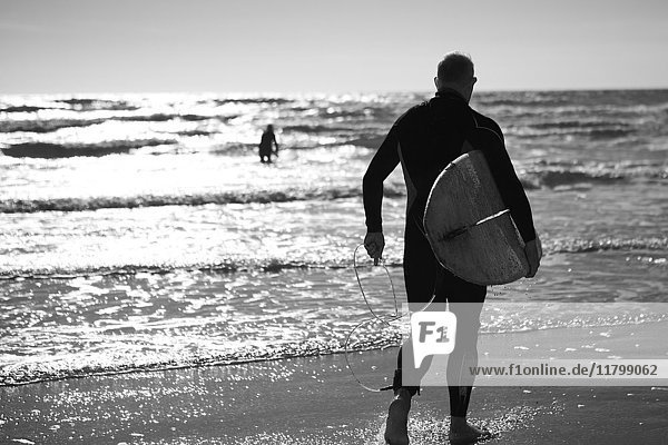 Rear view of man in wetsuit standing by the ocean  carrying surfboard.