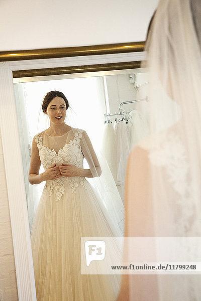 Eine Frau in einem Brautkleid  die vor dem Spiegel steht  in einer Brautboutique.