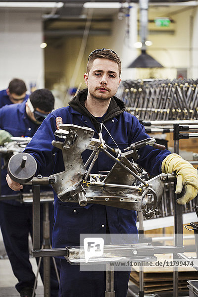 Male skilled factory worker in overalls wearing one protective glove  working on a bicycle frame in a factory.