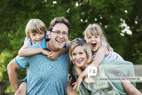Eltern  ein Mann und eine Frau  die in einem Garten stehen und ihren Sohn und ihre Tochter Huckepack nehmen.