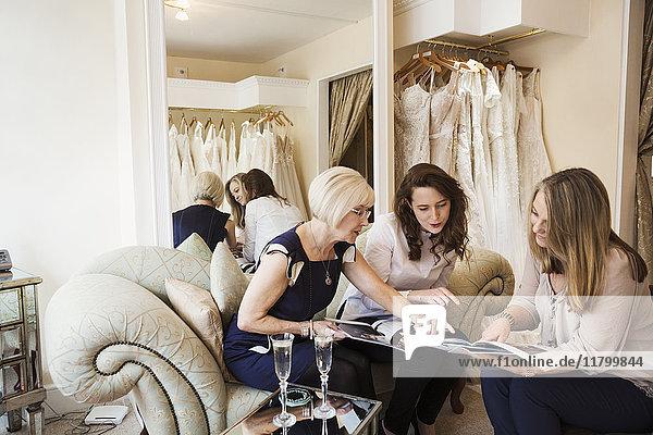 Drei Frauen in einem Brautkleidergeschäft  eine zukünftige Braut und zwei Einzelhandelsberaterinnen beim Durchblättern von Broschüren und Zeitschriften. Zwei Gläser Champagner auf dem Tisch.