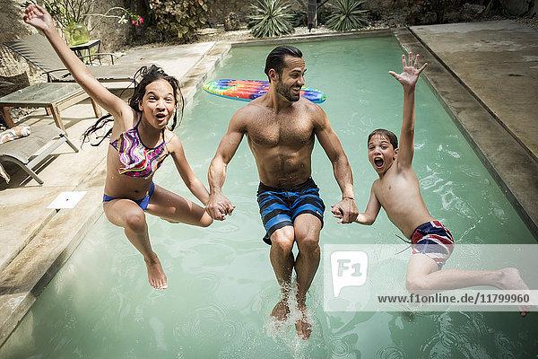 Ein Mann hält mit zwei Kindern  die rückwärts in ein Schwimmbecken springen  Händchen.