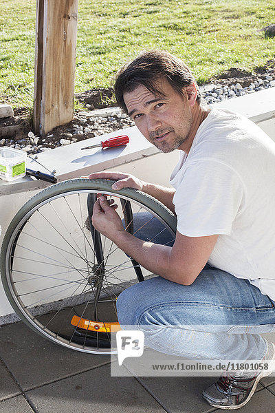 Man repairing bicycle wheel