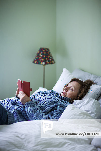 Woman in bed using cell phone