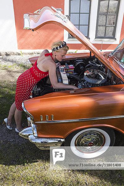 Woman repairing vintage car