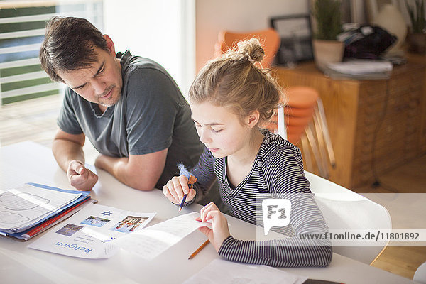 Father helping daughter with homework