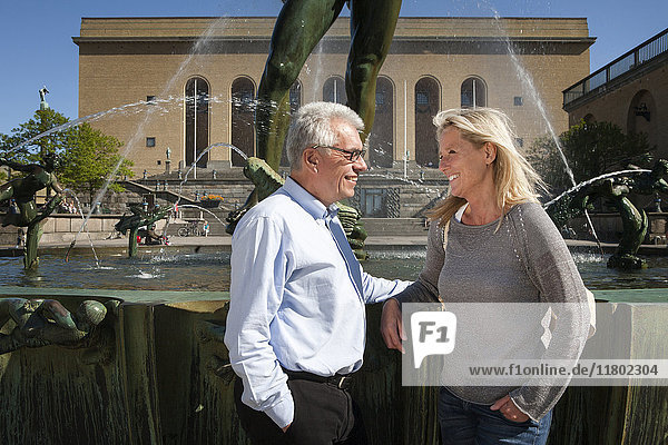 Mature couple standing next to fountain