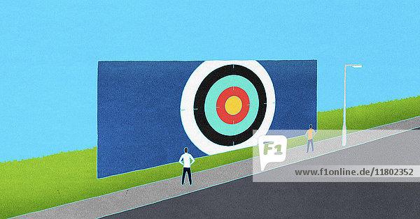 Zwei Menschen schauen auf eine Zielscheibe am Straßenrand