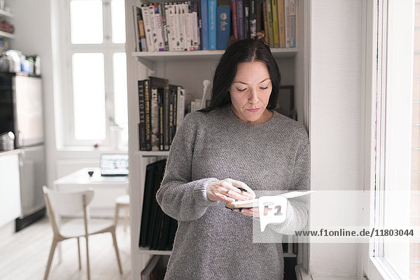 Woman holding note pad  standing by window