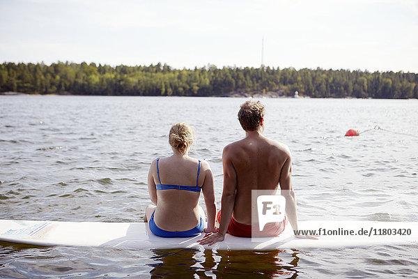 Couple sitting on paddleboard
