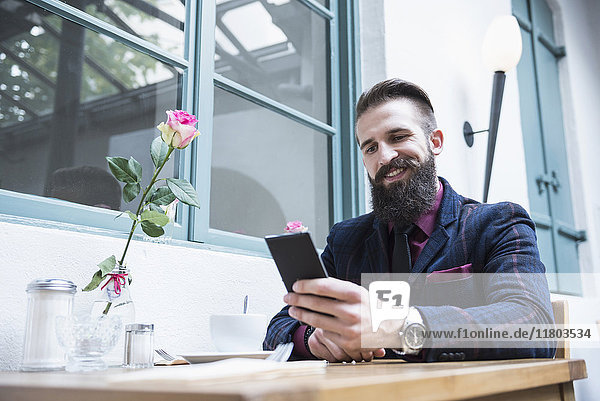 Young man smiling while using cell phone at cafe