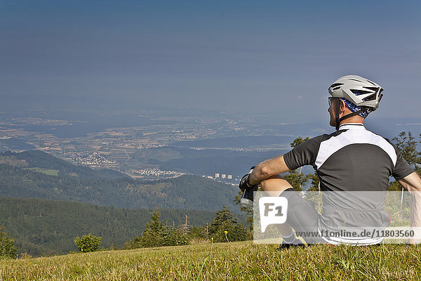 Mountain biker relaxing on meadow and looking at view in black forest