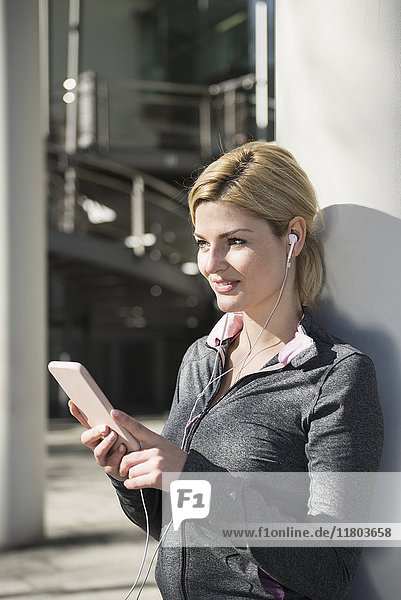 Woman in sportswear listening music on smart phone