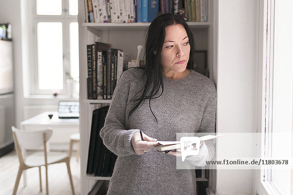 Woman holding note pad  looking through window