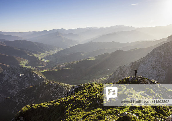 Man enjoying majestic view over mountains during hiking tour in Picos de Europa near the village of Potes  Cantabria  Spain