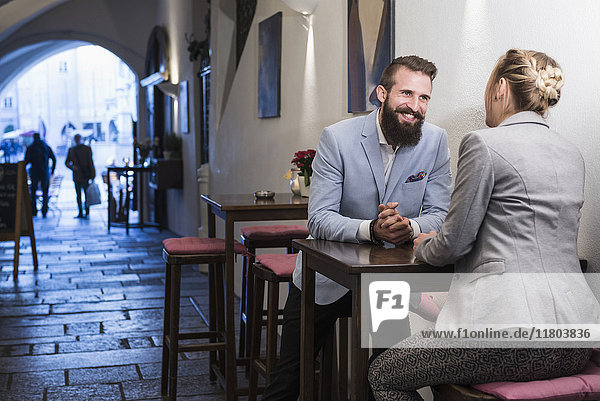 Young couple sitting on stool and talking at sidewalk cafe
