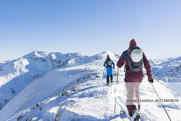 Rear view of skiers walking on ridge of mountain against sky