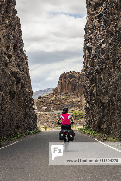 Rear view of woman riding electric bicycle on road amidst mountains