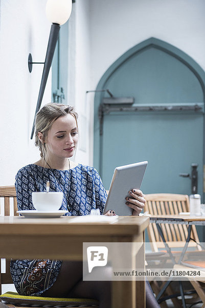 Young woman holding digital tablet at coffee shop