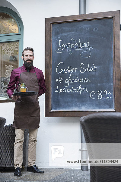 Young man standing by chalkboard menu in restaurant