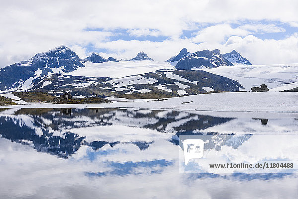 Snowy mountains reflecting in water