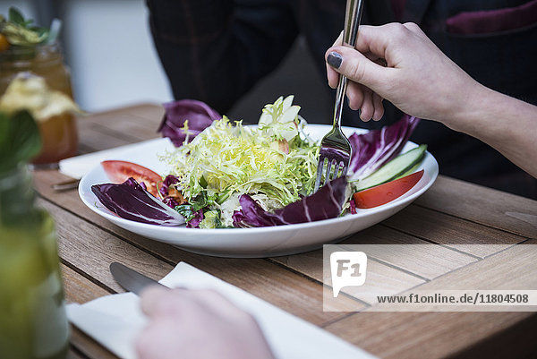Cropped image of woman holding fork and eating salad