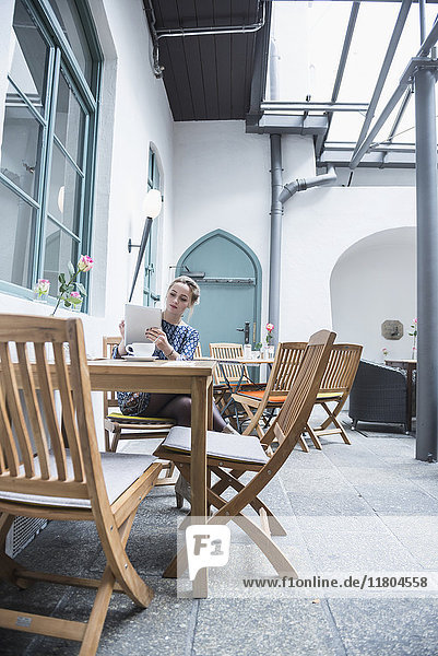Young woman using digital tablet at coffee shop