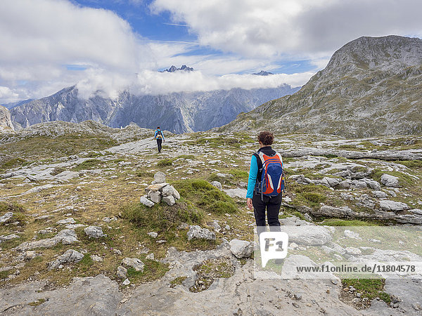 Woman and Man on hiking tour in Picos de Europa near Covadonga  Asturias  Northern Spain while In background is summit of Picu Urriellu