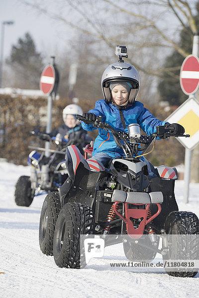 Boys riding quad bike on snow road