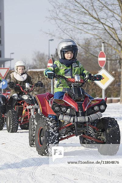 Children riding quad bike on snow