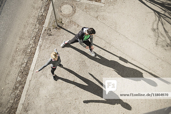 Man and woman in sportswear stretching outdoors