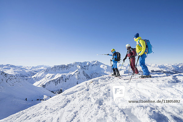 Skiers looking at the view on snow mountain