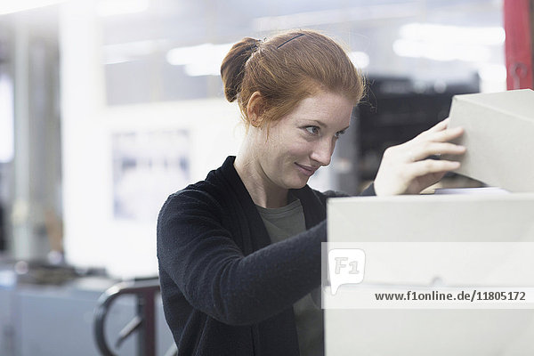 Attractive female worker opening box kept on top front heap of boxes at press