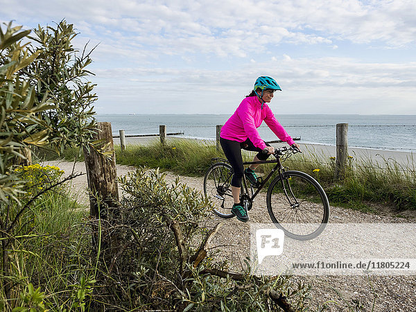 Woman riding bike against sea and sky