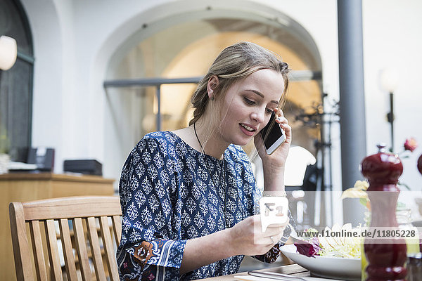 Young woman talking on mobile phone while eating salad at restaurant